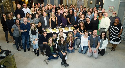 cast and crew with cake